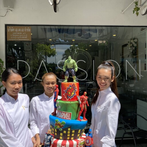 The Marvel superhero birthday cake being carried by our cake decorating team Anne, Kea and Muay
